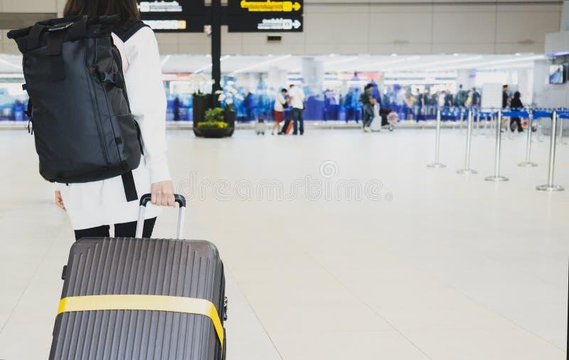 Молодая женщина вытягивая чемодан в крупном аэропорте Путешественник молодой женщины в международном аэропорте с чемоданом удержи стоковое фото