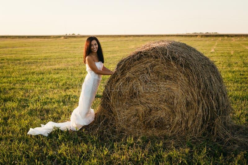 Молодая женщина в белой ткани около стога сена стоковое изображение rf