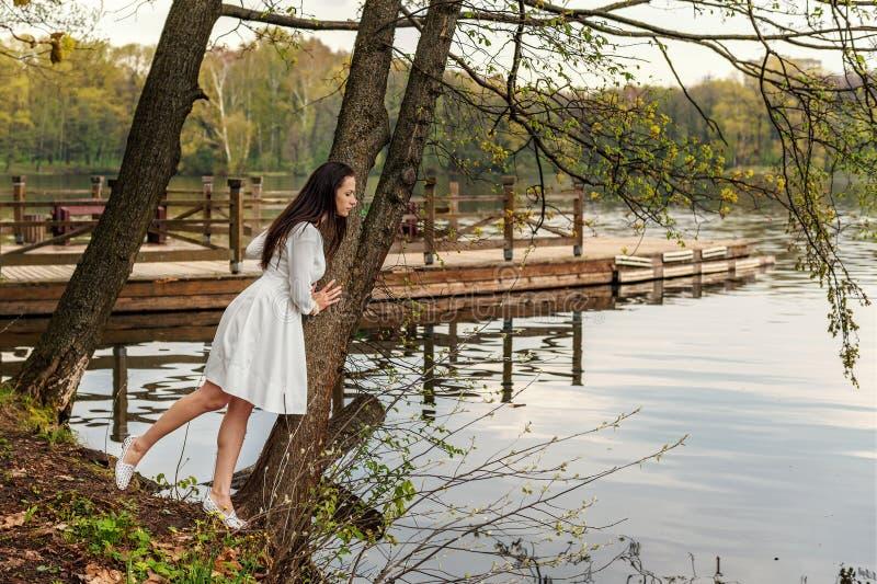 Молодая женщина в белом платье прильнула к дереву над озером и взглядам в речную воду стоковое изображение