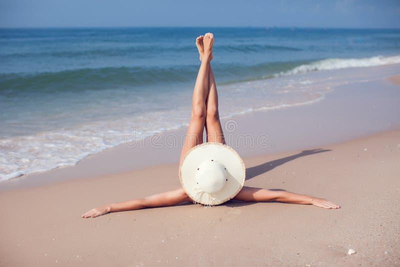 Молодая женщина в бикини и в соломенной шляпе лежа на тропическом bea стоковое изображение