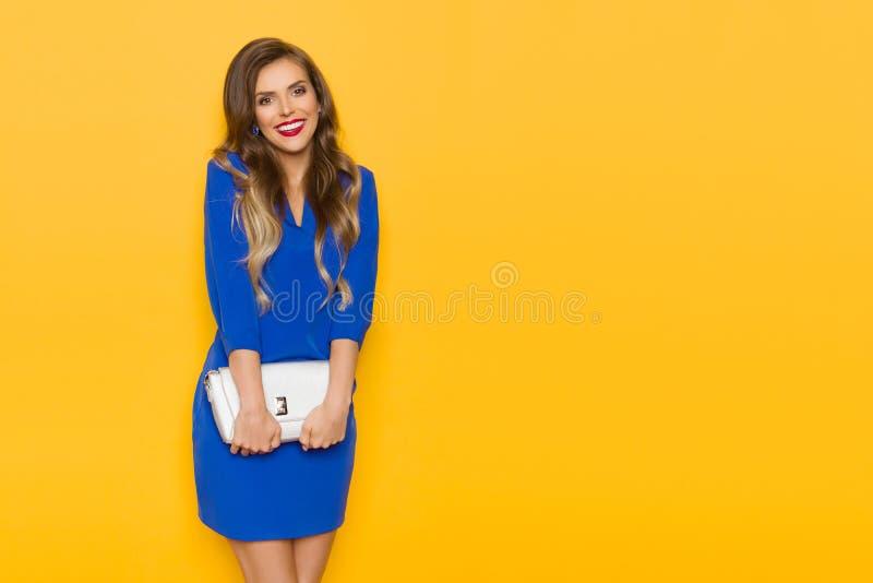 Молодая женщина в голубом мини платье держит бежевое портмоне, смотрящ камеру и усмехаться стоковое фото rf