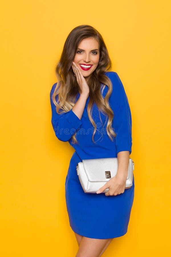 Молодая женщина в голубом мини платье держит серебряное портмоне, представляющ с рукой на Chin и усмехаться стоковые изображения
