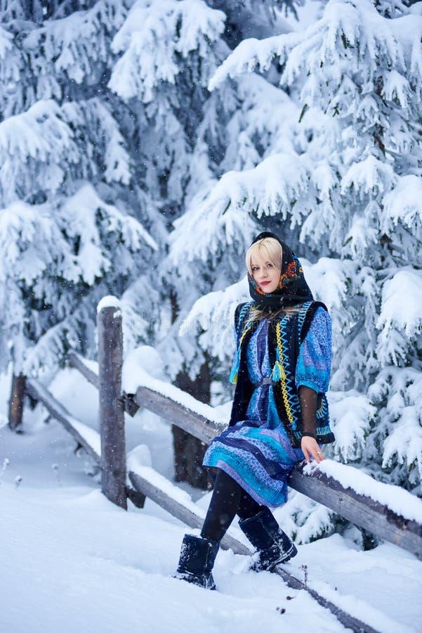 Молодая женщина в голубом платье, вышитой теплой безрукавной меховой шыбе и бандане с флористическим дизайном стоковое фото rf