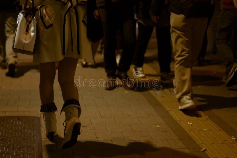 Молодая женщина в дизайнерской одежде идя группой в составе люди на ноче стоковое изображение rf