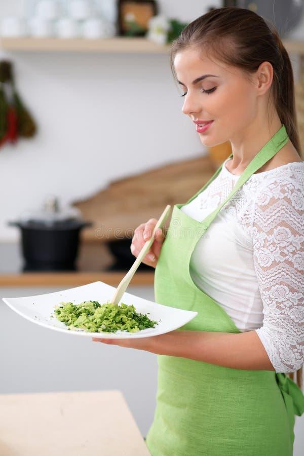 Молодая женщина в зеленой рисберме варит в кухне Домохозяйка пробует свежий салат деревянной ложкой стоковое изображение rf