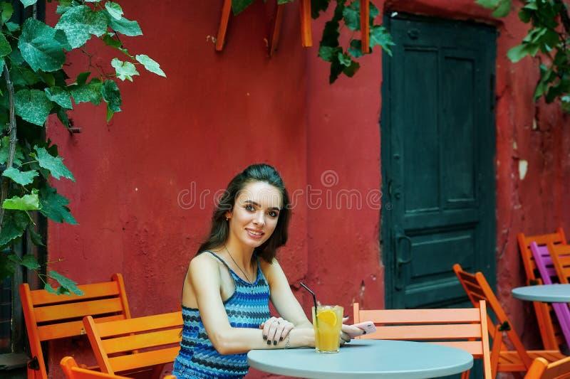 Молодая женщина в кафе улицы со стеклом освежающего напитка стоковые изображения rf