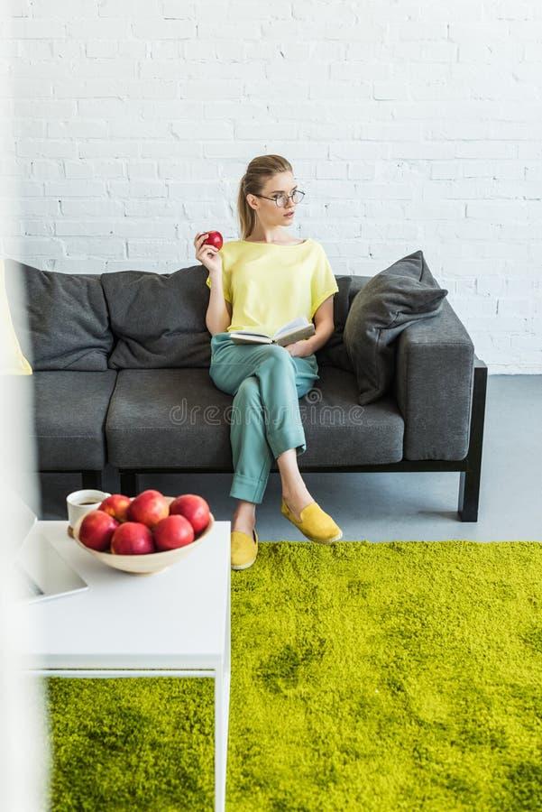 молодая женщина в книге чтения eyeglasses и яблоко удержания на софе около таблицы с яблоками и ноутбуком кофе стоковая фотография
