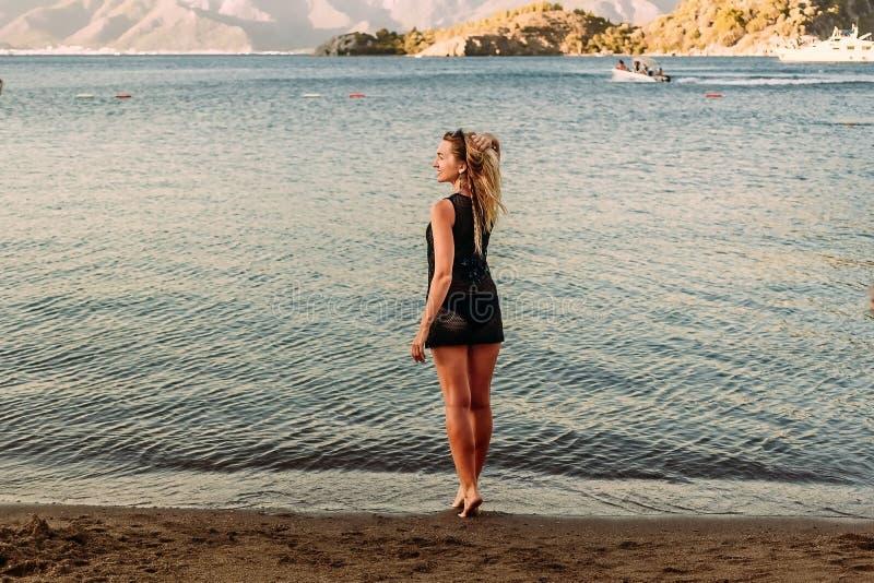 Молодая женщина в коротком платье стоит на пляже на заходе солнца стоковые изображения rf