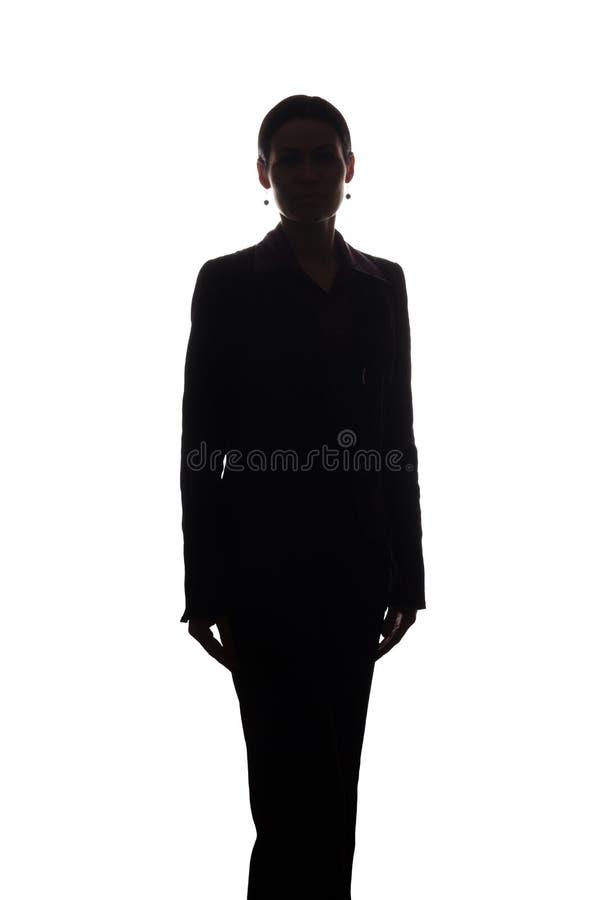 Молодая женщина в костюме, вид спереди - силуэте стоковое изображение rf