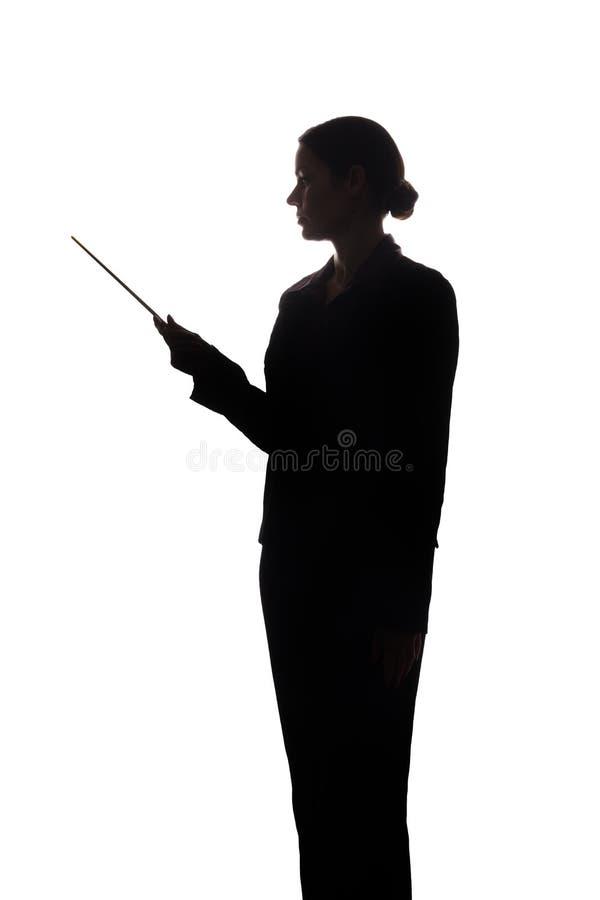 Молодая женщина в костюме показывает указатель вперед, взгляд со стороны - силуэт стоковое изображение rf