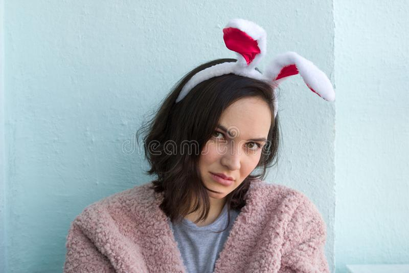 молодая женщина в костюме ушей зайчика розовой меховой шыбы нося белом против голубой предпосылки стоковое изображение rf