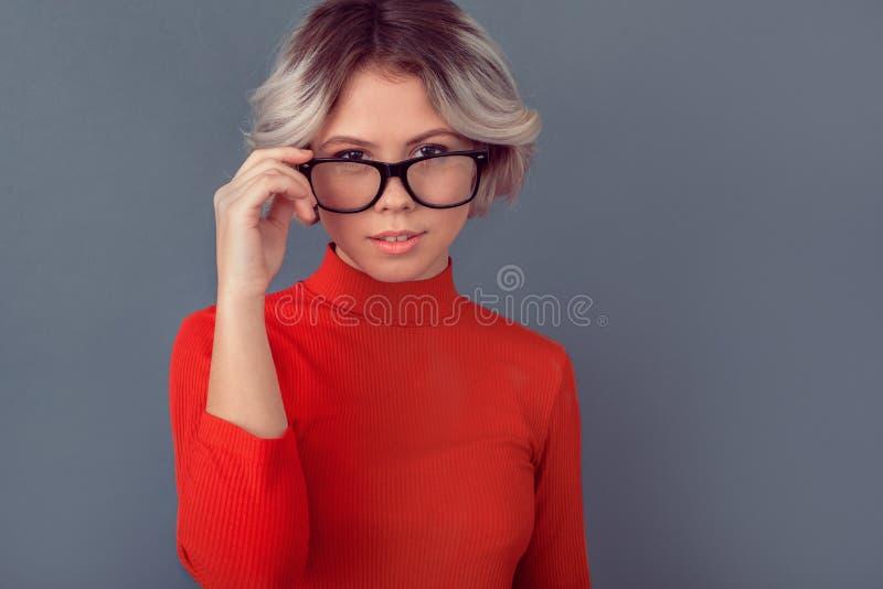 Молодая женщина в красной блузке изолированной на серых eyeglasses стены стоковое изображение