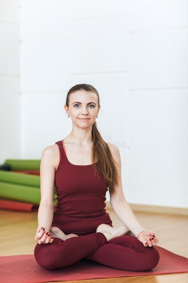 Молодая женщина в красном костюме смотря камеру и усмехаясь делающ тренировки в спортзале, представление Meditat йоги лотоса деву стоковое изображение