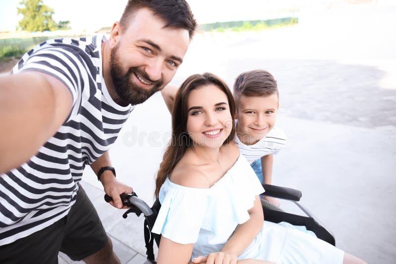 Молодая женщина в кресло-коляске с ее семьей принимая selfie outdoors стоковая фотография