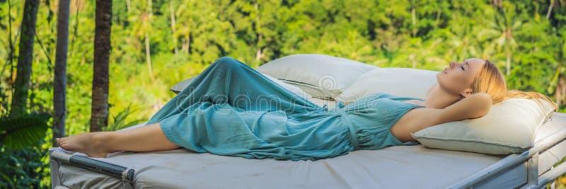 Молодая женщина в кровати над джунглями Интимность с ЗНАМЕНЕМ природы, ДЛИННЫЙ ФОРМАТ стоковые изображения