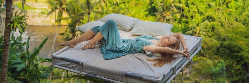 Молодая женщина в кровати над джунглями Интимность с ЗНАМЕНЕМ природы, ДЛИННЫЙ ФОРМАТ стоковая фотография rf