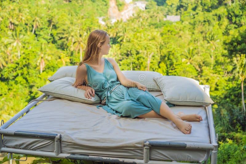 Молодая женщина в кровати над джунглями Интимность с природой стоковая фотография