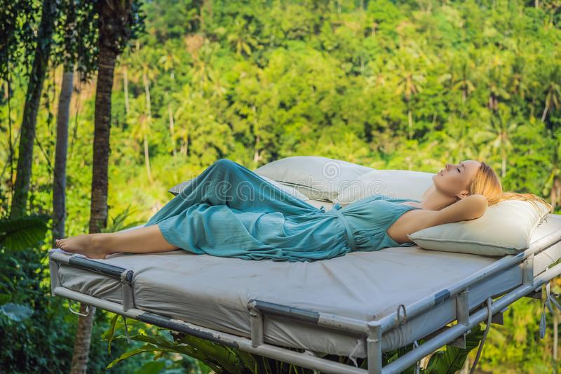 Молодая женщина в кровати над джунглями Интимность с природой стоковые фото