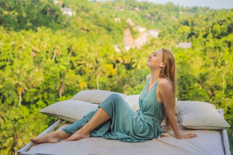 Молодая женщина в кровати над джунглями Интимность с природой стоковая фотография rf