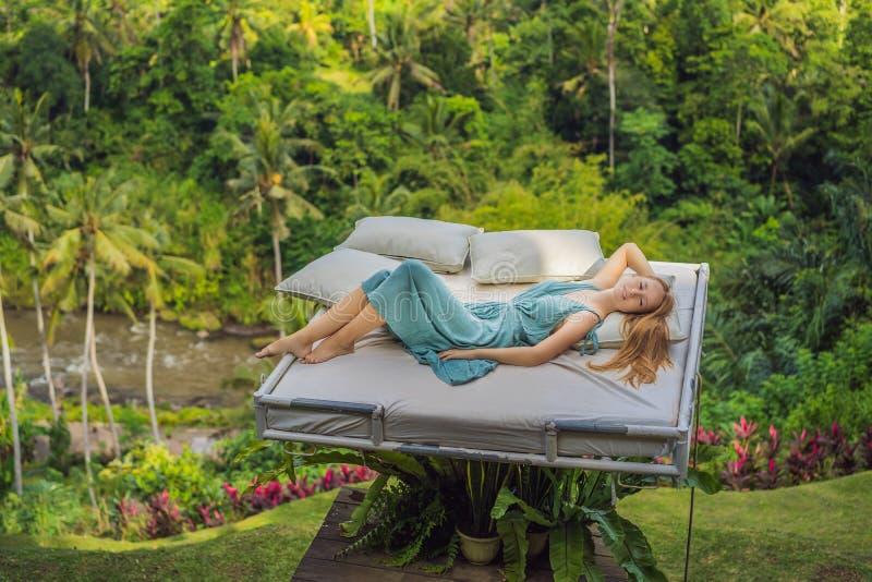 Молодая женщина в кровати над джунглями Интимность с природой стоковые изображения rf