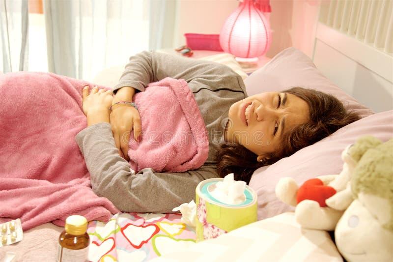 Молодая женщина в кровати чувствуя съемку средства проблемы менструации сильного живота больную стоковое изображение