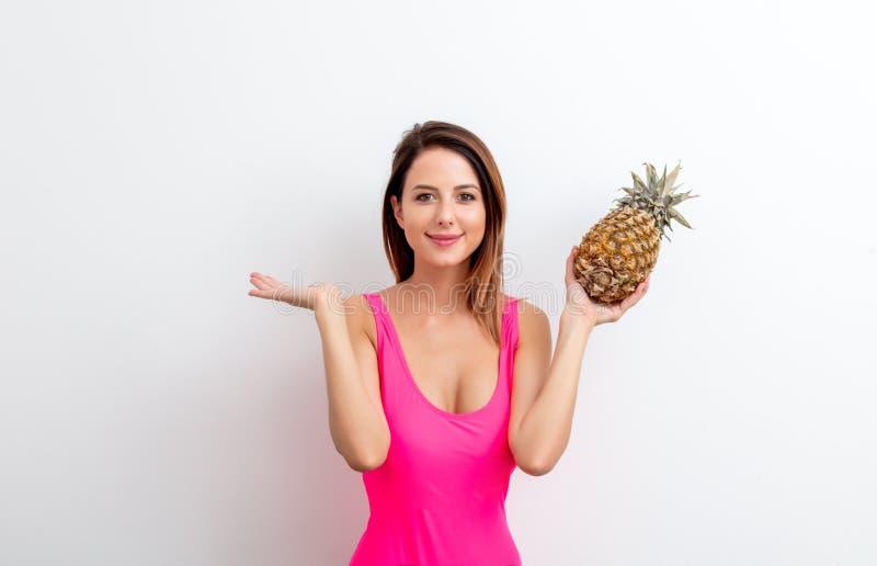 Молодая женщина в купальнике с ананасом стоковые изображения