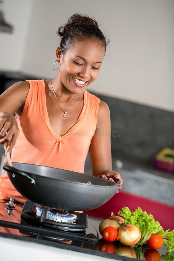Молодая женщина в кухне подготавливая еду стоковые фотографии rf