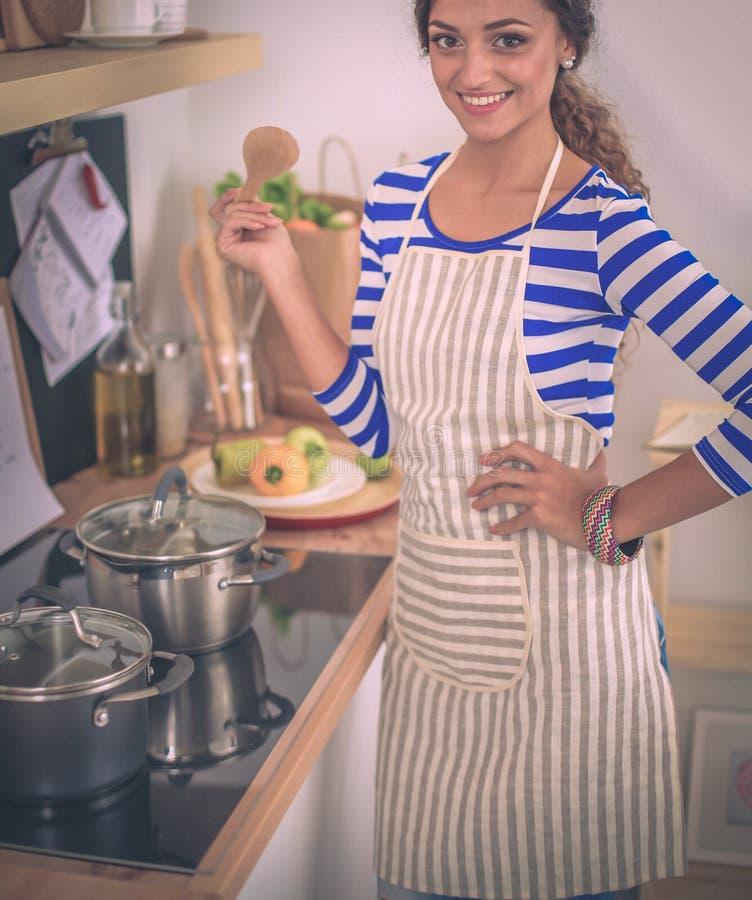 Молодая женщина в кухне подготавливая еду стоковая фотография