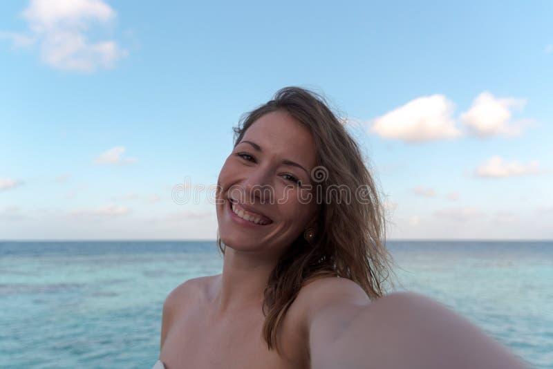 Молодая женщина в медовом месяце принимая selfie Море как предпосылка стоковая фотография rf