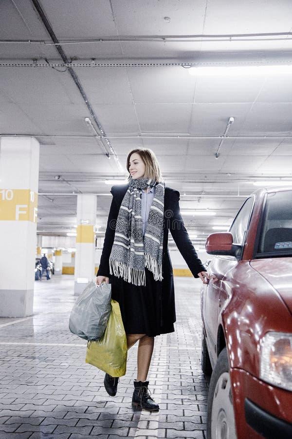 Молодая женщина в месте для стоянки около автомобиля Девушка после ходить по магазинам стоковое изображение