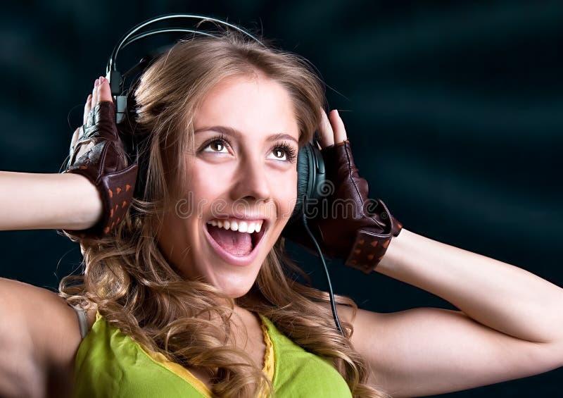 Молодая женщина в наушниках пея стоковые изображения rf