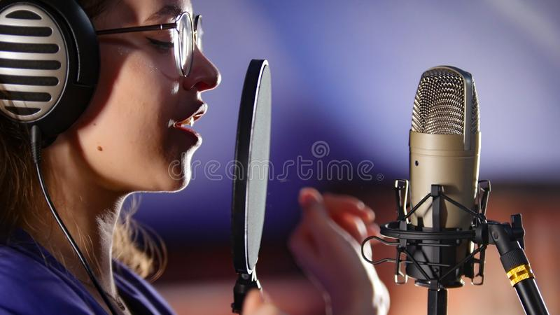 Молодая женщина в наушниках поя через поп-фильтр в студии стоковое фото rf