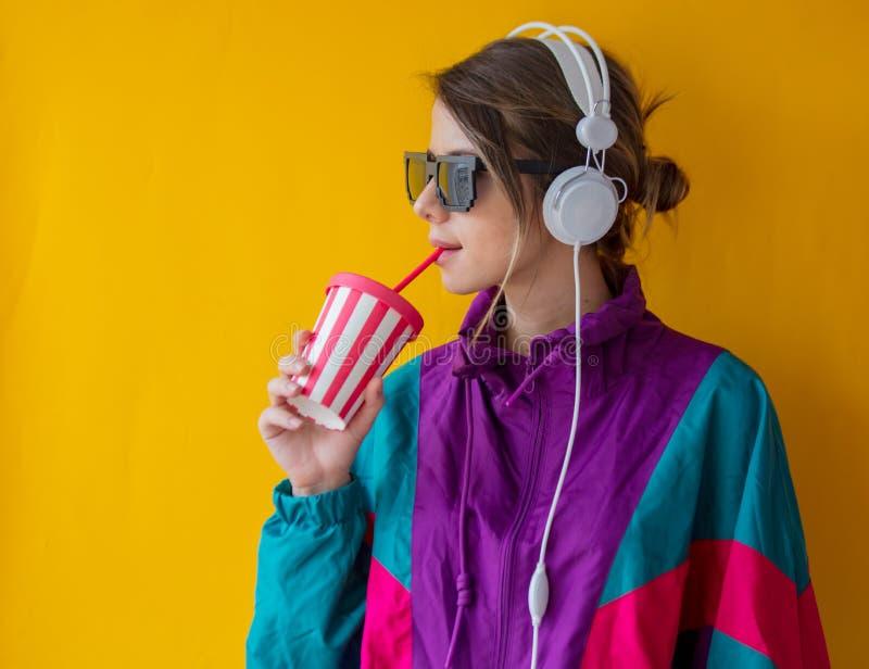 Молодая женщина в одеждах стиля 90s с чашкой и наушниками стоковая фотография