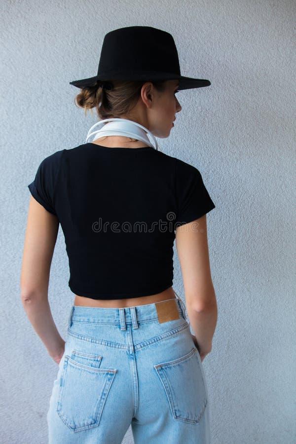 Молодая женщина в одеждах шляпы и стиля 90s стоковое фото rf