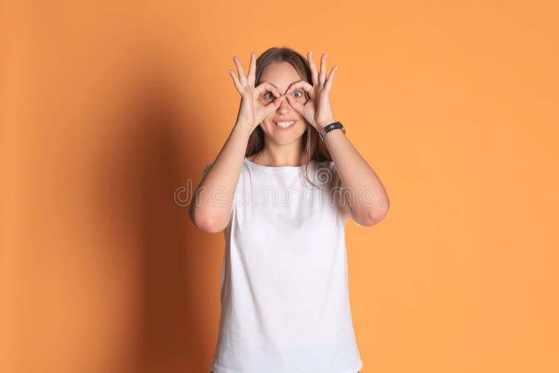 Молодая женщина в основной одежде усмехаясь смотрящ камеру через отверстия сделанные с пальцами над желтой предпосылкой стоковое изображение rf