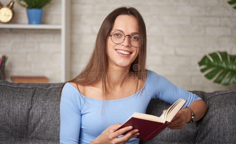 молодая женщина в очках читает книгу дома стоковое изображение rf