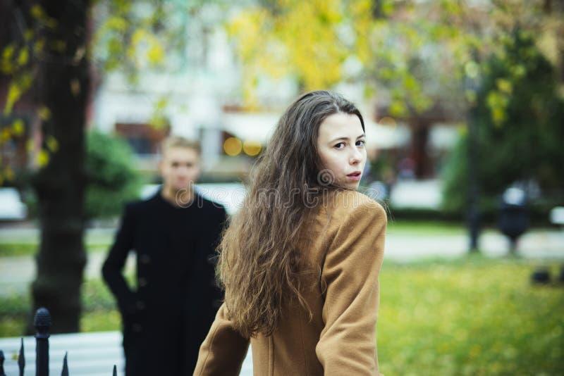 Молодая женщина в пальто верблюда идет к парню в парке стоковые изображения rf
