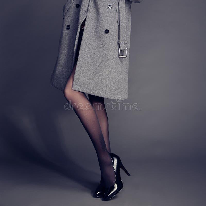 Молодая женщина в пальто с красивыми ногами стоковые изображения rf