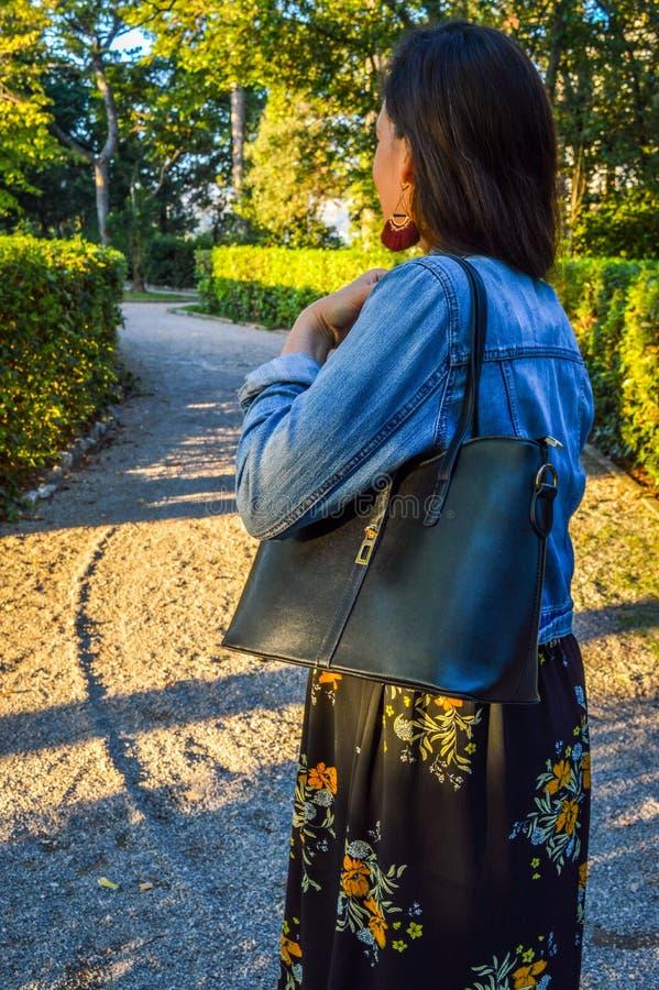 Молодая женщина в парке, носящ флористическое платье и куртку джинсовой ткани, держа черную сумку стоковые фото