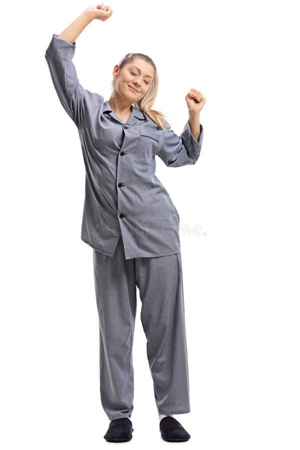 Молодая женщина в пижамах протягивая стоковое изображение rf