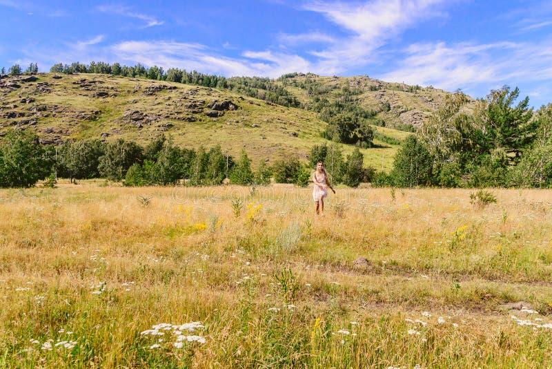 Молодая женщина в платье лета бежит через поле в лете стоковое изображение