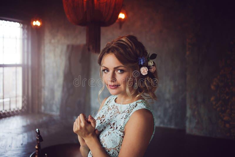 Молодая женщина в платье шнурка и ее волосы украшенные с цветками стоковые фото