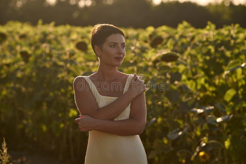 Молодая женщина в поле солнцецветов на заходе солнца стоковые изображения rf