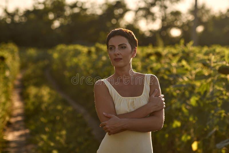 Молодая женщина в поле солнцецветов на заходе солнца стоковая фотография