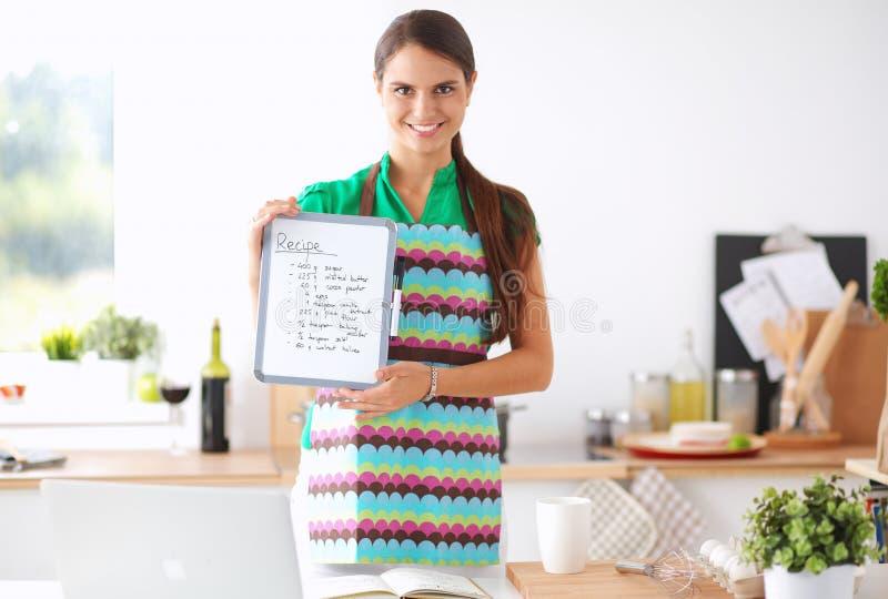 Молодая женщина в рисберме варит в кухне стоковое фото rf