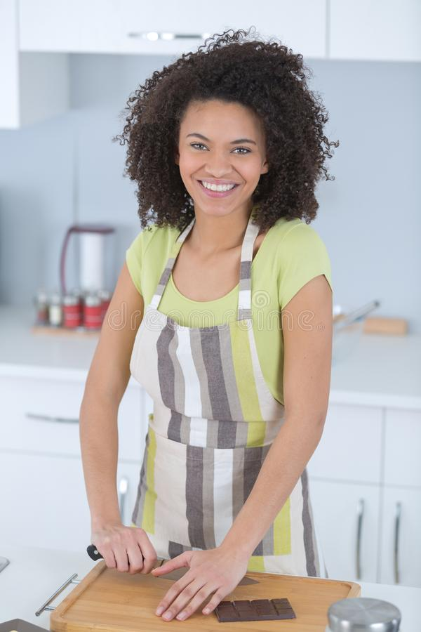 Молодая женщина в рисберме варя в кухне стоковая фотография rf