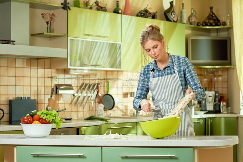 Молодая женщина в рисберме, кухне стоковое изображение