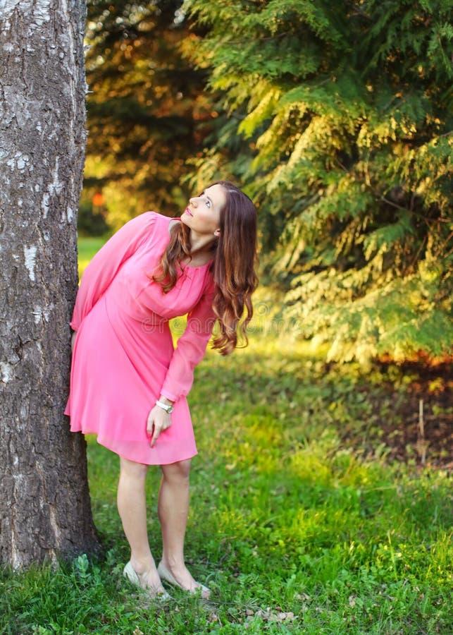 Молодая женщина в розовом платье, полагающся к дереву, смотря вверх, с солнцем стоковое изображение
