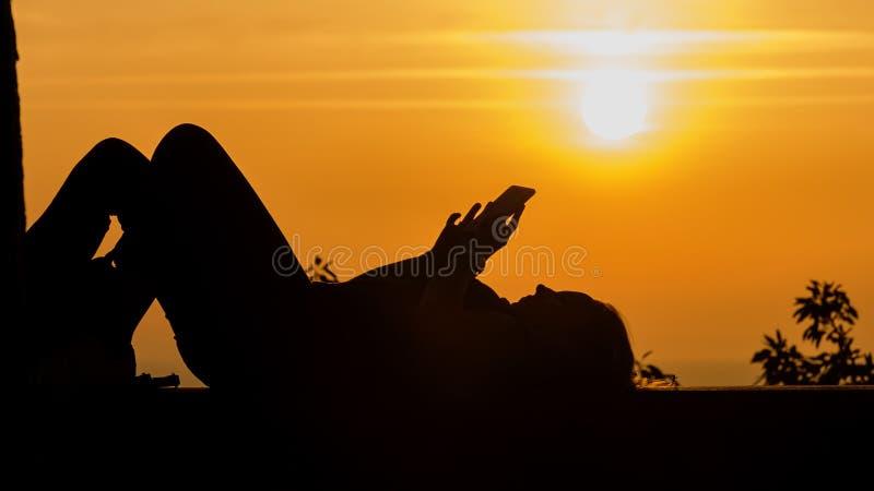 Молодая женщина в силуэте использует смартфон лежа в установке солнца над морем стоковое фото rf