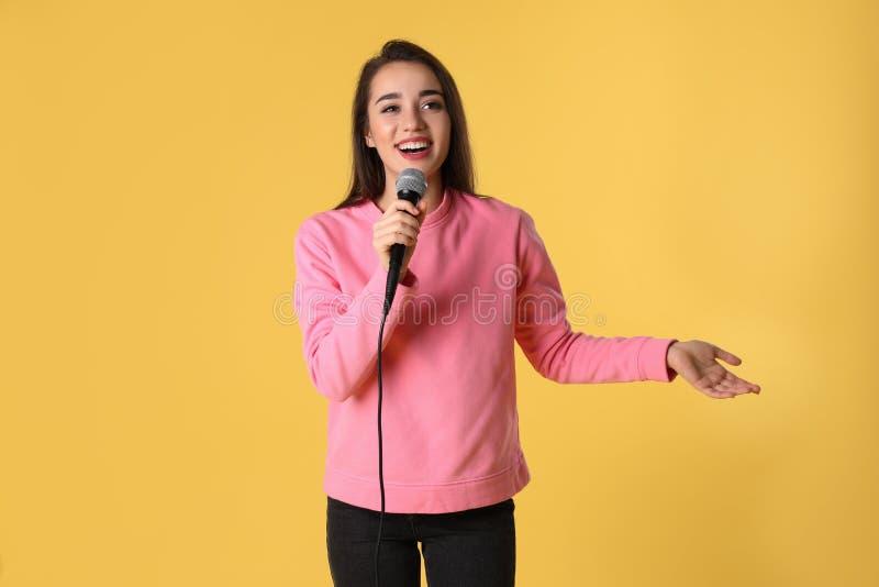 Молодая женщина в случайных одеждах представляя с микрофоном стоковые изображения